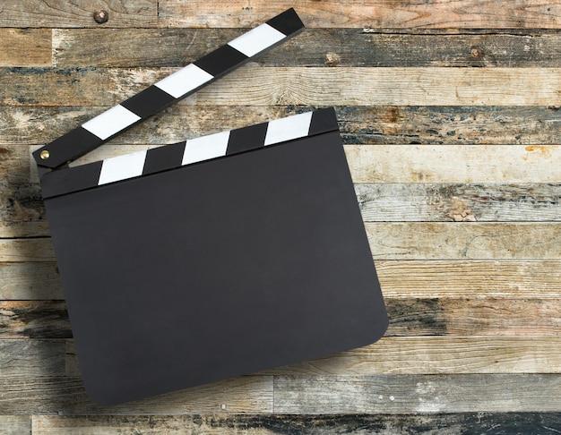 Claquete de produção de filme em branco sobre fundo de madeira com
