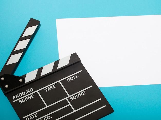 Claquete de produção de filme sobre fundo azul.