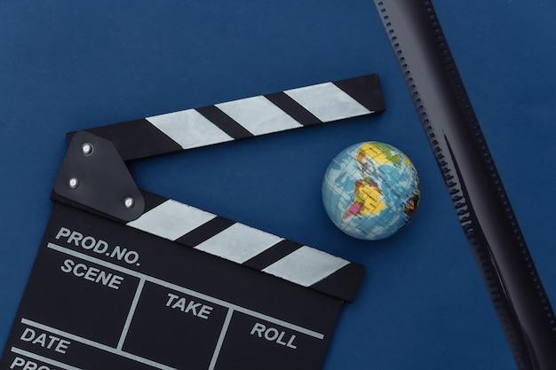Claquete do filme com globo, fita do filme no fundo azul clássico. cinema, produção de cinema, indústria do entretenimento. cor 2020. vista superior