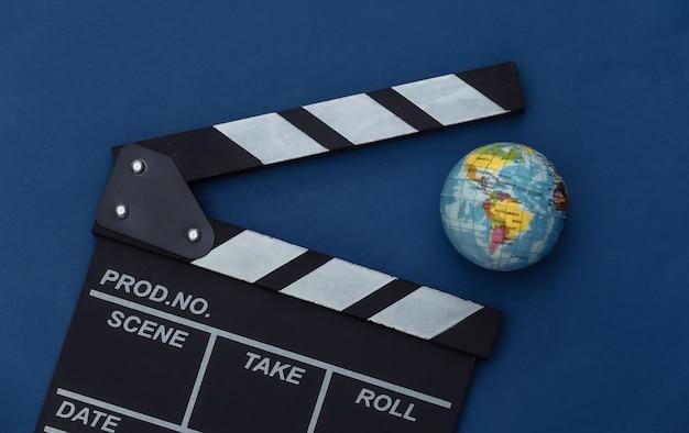 Claquete do filme com globo no fundo azul clássico. cinema, produção de cinema, indústria do entretenimento. cor 2020. vista superior