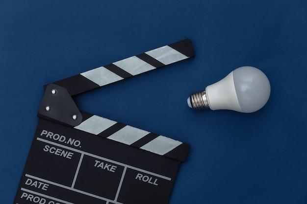 Claquete do filme com lâmpada no fundo azul clássico. cinema, produção de cinema, indústria do entretenimento. cor 2020. vista superior