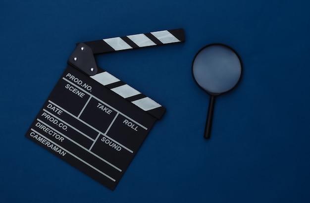 Claquete do filme com lupa no fundo azul clássico. cinema, produção de cinema, indústria do entretenimento. cor 2020. vista superior