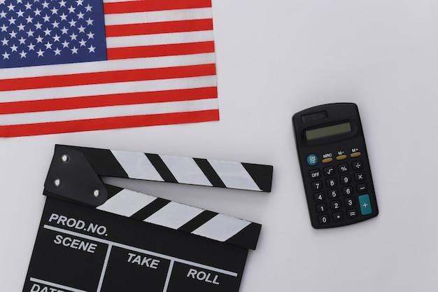 Claquete do filme e calculadora, bandeira dos eua em fundo branco. taxas de cinema. cinema, produção de filmes. vista do topo