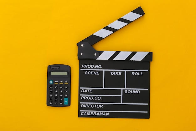 Claquete do filme e calculadora em fundo amarelo. taxas de cinema. cinema, produção de filmes. vista do topo