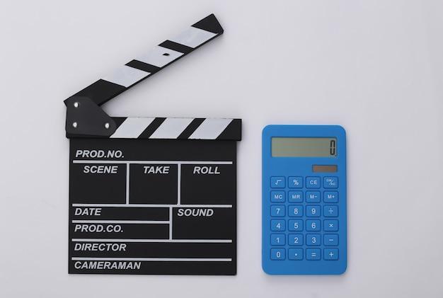 Claquete do filme e calculadora em fundo branco. taxas de cinema. cinema, produção de filmes. vista do topo