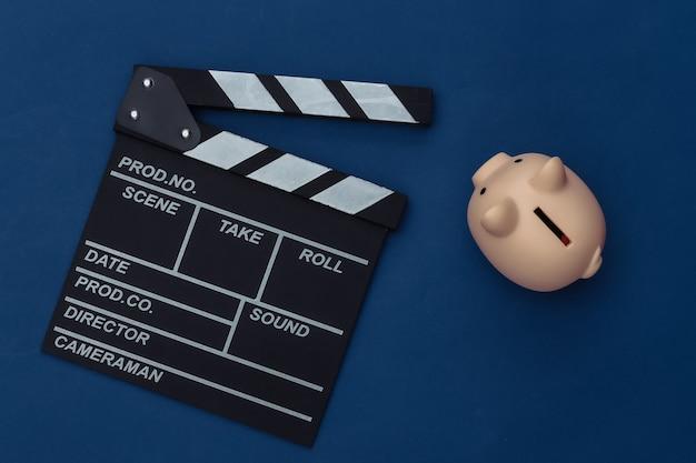 Claquete do filme e cofrinho em fundo azul clássico. cinema, orçamento de cinema, indústria do entretenimento. cor 2020. vista superior