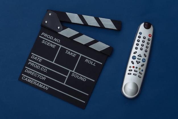 Claquete do filme e controle remoto da tv no fundo azul clássico. cinema, produção de cinema, indústria do entretenimento. cor 2020. vista superior