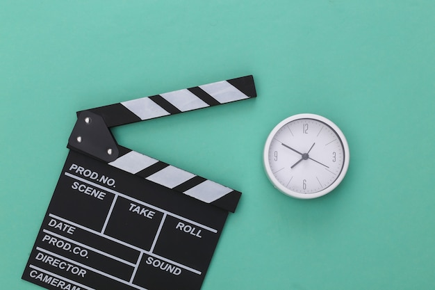 Claquete do filme e despertador em um fundo azul pastel. cinema, produção de cinema, indústria do entretenimento. vista do topo