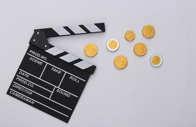 Claquete do filme e moedas em fundo branco. taxas de cinema. cinema, produção de filmes. vista do topo