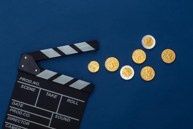 Claquete do filme e moedas no fundo azul clássico. taxas de cinema. cinema, produção de filmes. vista do topo