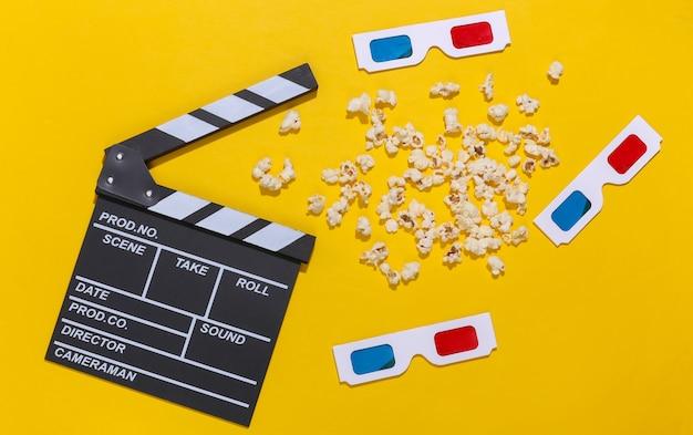 Claquete do filme, pipoca e óculos 3d em fundo amarelo com sombras profundas. indústria do entretenimento. vista do topo