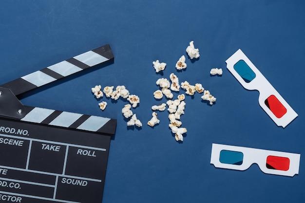 Claquete do filme, pipoca e óculos 3d no fundo azul clássico com sombras profundas. indústria do entretenimento. vista do topo