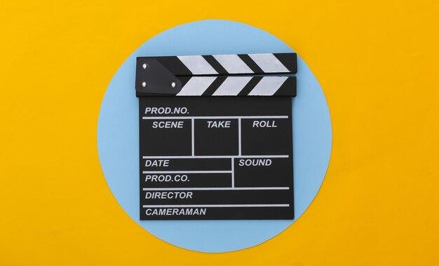 Claquete do filme sobre fundo azul amarelo. cinema, produção de cinema, indústria do entretenimento. vista do topo