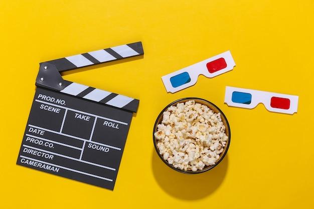 Claquete do filme, tigela de pipoca e óculos 3d em fundo amarelo com sombras profundas. indústria do entretenimento. vista do topo