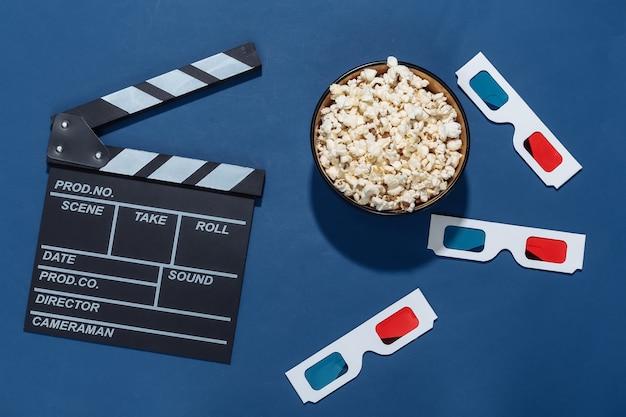 Claquete do filme, tigela de pipoca e óculos 3d no fundo azul clássico com sombras profundas. indústria do entretenimento. vista do topo