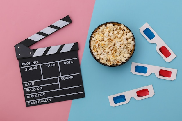 Claquete do filme, tigela de pipoca, óculos 3d em fundo azul rosa. indústria do entretenimento. vista do topo. postura plana