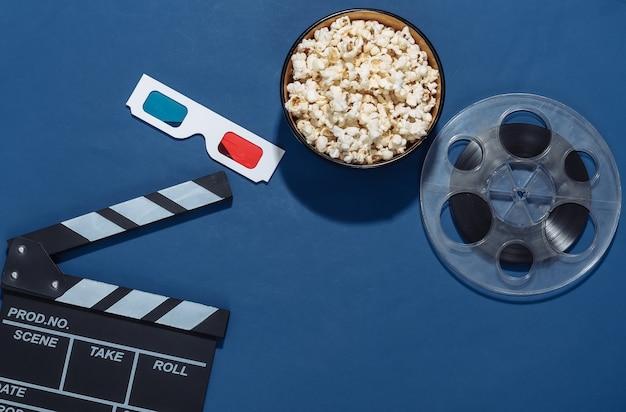 Claquete do filme, tigela de pipoca, rolo de filme e óculos 3d no fundo azul clássico com sombras profundas. indústria do entretenimento. vista do topo