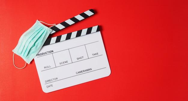 Claquete e máscara facial em fundo vermelho. é usado na produção de vídeo ou na indústria de cinema e cinema.