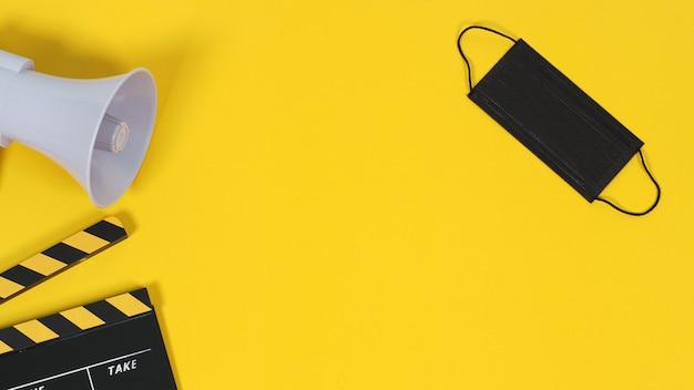 Claquete e máscara facial preta e megafone em fundo amarelo. cor amarela e preta.