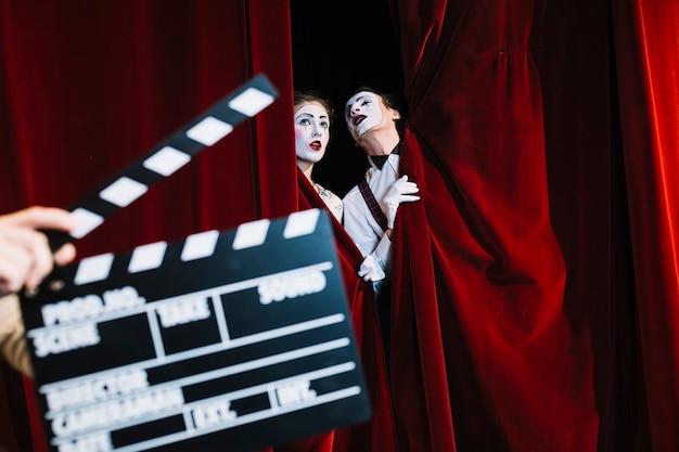 Claquete na frente do casal mime em pé atrás da cortina vermelha