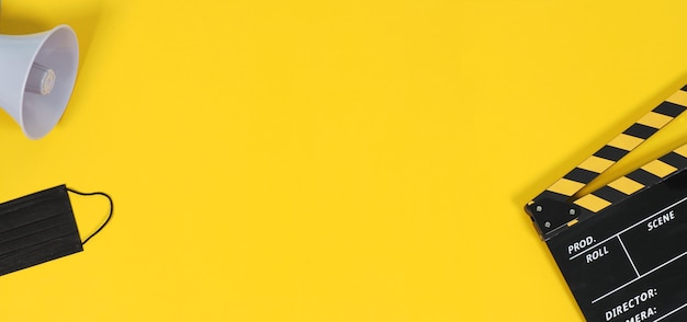 Claquete ou ardósia do filme e máscara facial preta e megafone em fundo amarelo. cor amarela e preta.