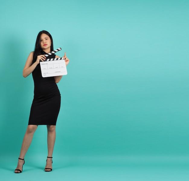 Claquete ou claquete de filme na mão de uma adolescente ou mulher em fundo verde hortelã