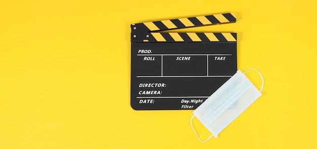 Claquete ou claquete de filme ou ardósia e máscara facial em fundo amarelo.