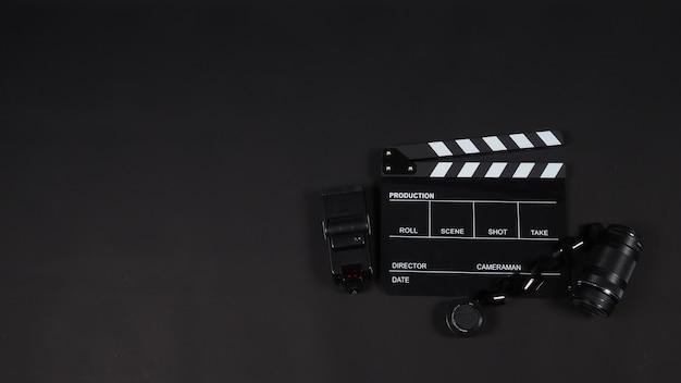 Claquete ou claquete ou filme ardósia com filme, lente, flash light. é usado na produção de vídeo, indústria do cinema em fundo preto.