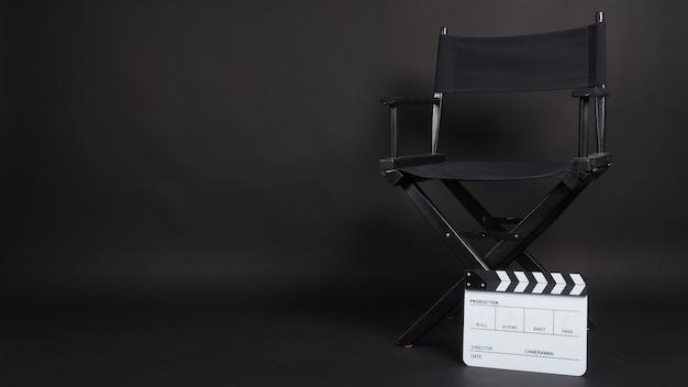 Claquete ou claquete ou quadro de filme com cadeira do diretor, use na produção de vídeo, cinema, indústria do cinema em fundo preto