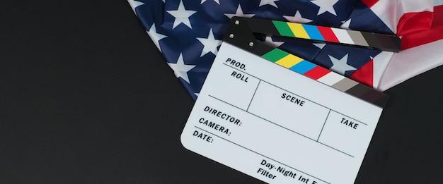 Claquete ou filme e bandeira dos estados unidos da américa (eua) em fundo preto.