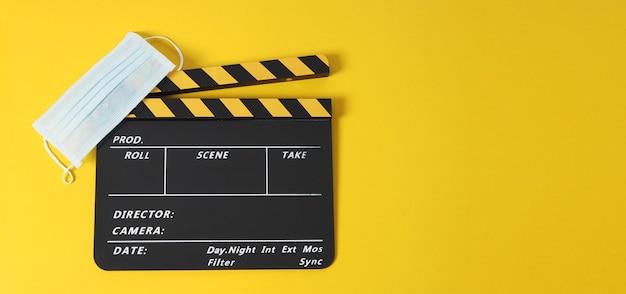 Claquete ou filme e máscara facial em fundo amarelo.