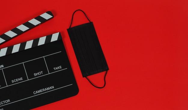 Claquete ou filme e máscara preta em fundo preto vermelho.