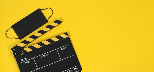 Claquete ou filme e máscara preta sobre fundo amarelo. cor amarela e preta.
