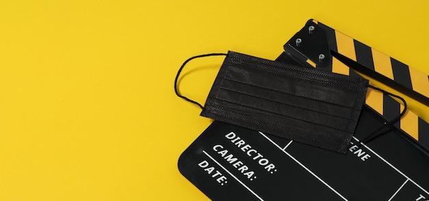 Claquete ou filme e máscara preta sobre fundo preto amarelo. cor amarela e preta.