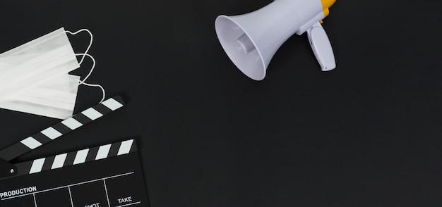 Claquete ou quadro de filme preto e máscara facial, megafone em background.it preto usa na produção de vídeo e na indústria do cinema.