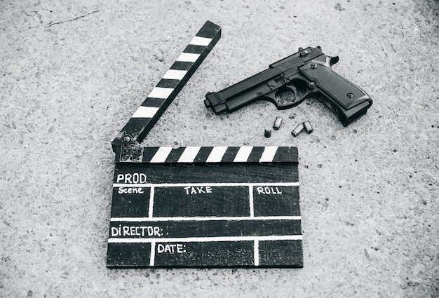 Claquete preta com arma no fundo. direção e filmagem de filme de cinema. história de detetive criminal.