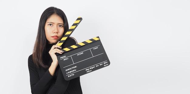 Claquete preta ou claquete de filme em mão de mulher asiática. ela usa na produção de vídeo