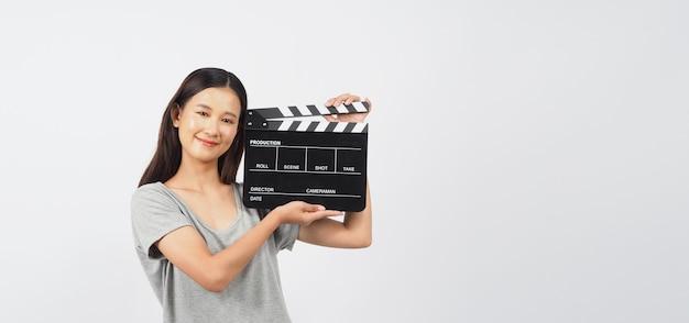 Claquete preta ou claquete do filme na mão de uma adolescente ou mulher. ele usa na produção de vídeo, indústria do cinema em fundo branco.