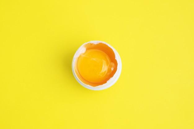 Clara de ovo de galinha crua e gema em meia casca em amarelo
