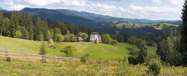 Clareira verde montanhosa de verão com pequena propriedade rural (vila de slavske, mts dos cárpatos, ucrânia). imagem composta de seis tiros.