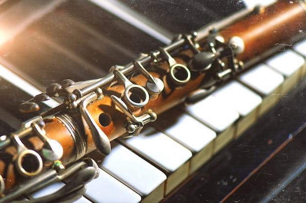 Clarinete antigo, apoiando-se no teclado de piano