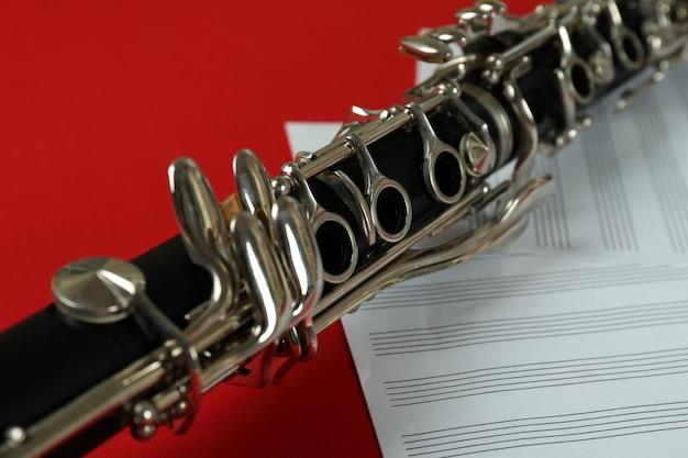 Clarinete e partituras em fundo vermelho.