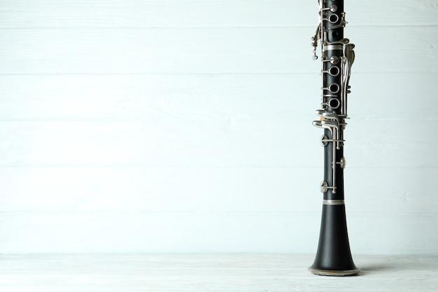 Clarinete em fundo branco de madeira, espaço para texto.