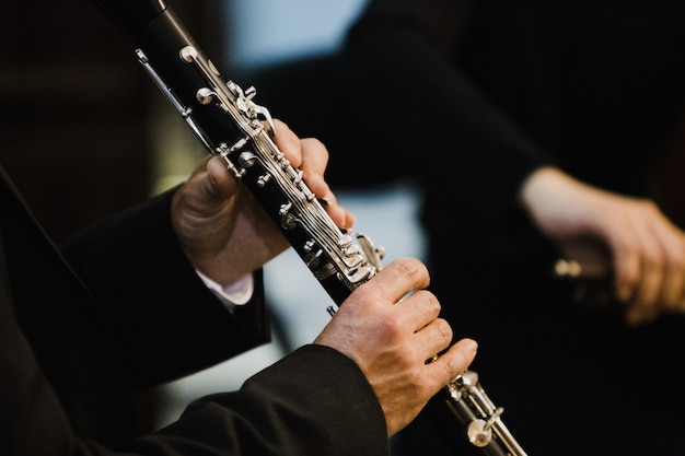 Clarinetista segurando uma flauta transversal de metal nas mãos.