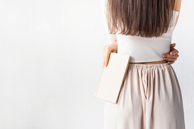 Claro e arejado. mulher jovem e bonita com cabelo comprido em roupas brancas aconchegantes sobre fundo branco, segurando um livro, vista de trás