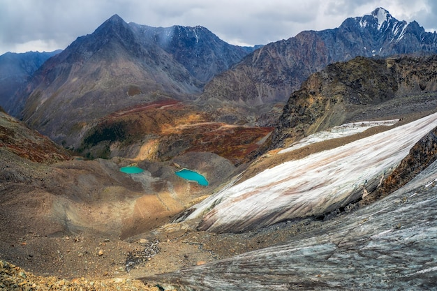 Claro-escuro da montanha. impressionante paisagem montanhosa escura com uma enorme montanha nevada e uma geleira iluminada pelo sol entre rochas altas. impressionante cenário alpino com uma grande geleira e lagos.