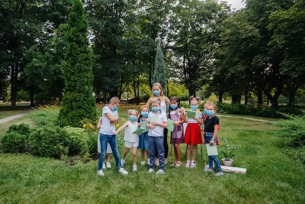 Classe de alunos mascarados envolvidos em treinamento ao ar livre durante a epidemia