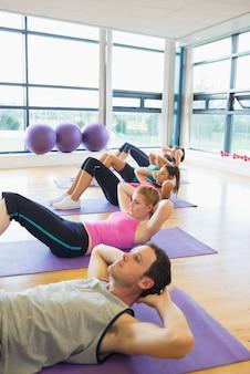 Classe de ginástica desportiva fazendo sentar-se em tapetes de exercícios