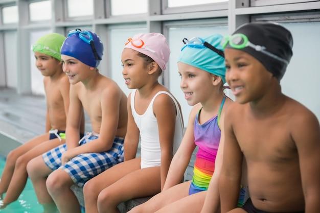 Classe de natação bonito sorrindo à beira da piscina