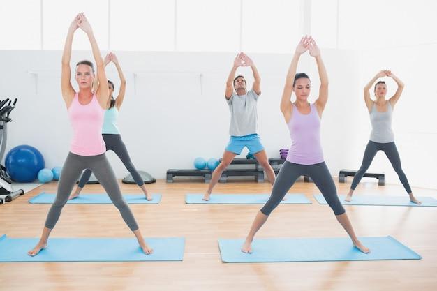Classe desportiva fazendo exercícios de pilate no estúdio de fitness